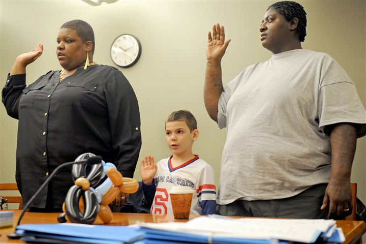 1123mhAdoptionDayLocal03-2 Eight-year-old Zackery is sworn in with his adoptive parents Sandy, left, and Kizzy Hazlip Saturday at the Allegheny County Family Law Center, Downtown.