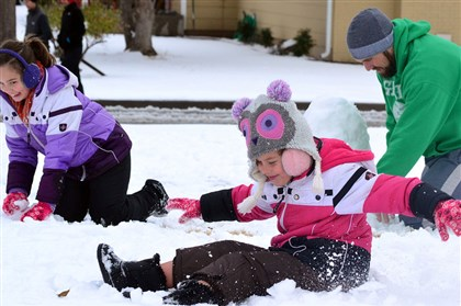 Severe Weather Photo Gallery Children and their father play in the snow Sunday in Lawton, Okla. A large storm blamed for at least eight deaths slogged through parts of the Southwest as it slowly churned east ahead of Thanksgiving.