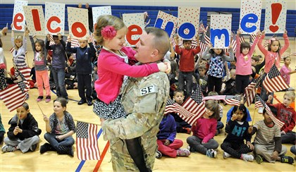 20131125radDadReturnsLocal06-5 Chartiers Valley Primary School first grader Autumn Schwiederowski is back in the arms of her father, Air Force Staff Sgt. Adam Schwiederowski, after he made a surprise return from overseas at her school.
