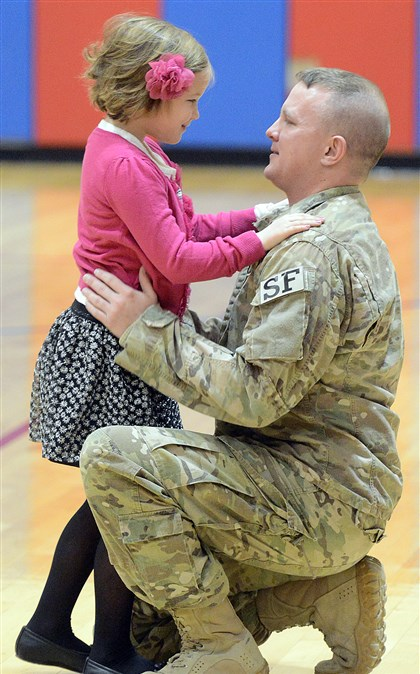20131125radDadReturnsLocal03-2 Chartiers Valley Primary School first grader Autumn Schwiederowski greets her father, Air Force Staff Sgt. Adam Schwiederowski, after he revealed himself as the Mystery Reader of a Thanksgiving-themed children's book for first grade classes.