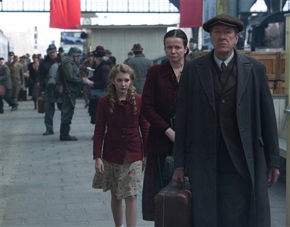 "bookthief1127-1 Liesel (Sophie Nelisse) meets her new foster parents, Hans (Geoffrey Rush) and Rosa (Emily Watson), in ""The Book Thief."""