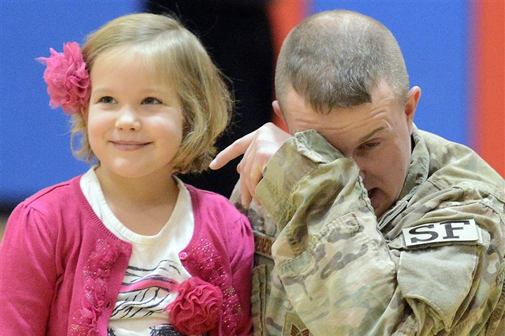 20131125radDadReturnsLocal04-3 Air Force Staff Sgt. Adam Schwiederowski wipes away tears after he greeted his daughter, Autumn, a first grader at Chartiers Valley Primary School, Monday morning.