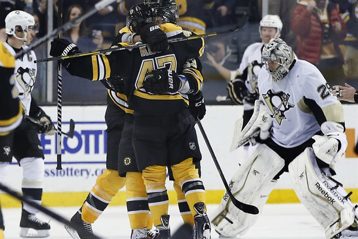 pens1126e-1 Teammates hug Bruins defenseman Torey Krug to celebrate his game-winning goal in overtime, as Penguins goalie Marc-Andre Fleury, right, skates off the ice.