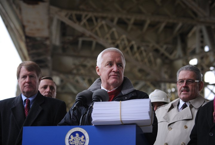 20131125jrGovLocal1 Gov. Tom Corbett, center, stands underneath Liberty Bridge on Monday with a stack of papers — the list of projects that need to be funded — during a news conference about the new transportation funding bill. Repairs to roadways will begin under a $2.3 billion transportation funding plan signed into law by Mr. Corbett.