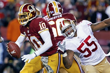 49ers Redskins Football Washington Redskins quarterback Robert Griffin III scrambles away from San Francisco 49ers outside linebacker Ahmad Brooks during the first half of an NFL football game in Landover, Md., on Nov. 25.