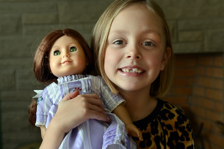 "20131126dsNDOLLznorth Mayzie Bonfili, 6, of McCandless, holds American Doll ""Felicity, "" her friend for the week. Northland Public Library in McCandless has a program that allows girls to borrow American Girl dolls for a week, just like taking out a book."