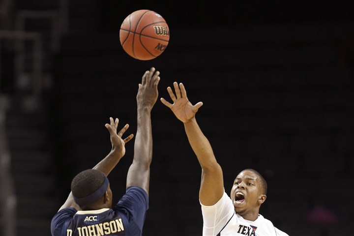 Pittsburgh Texas Tech Basketball Texas Tech guard Toddrick Gotcher tries to block a 3-point shot by Pitt forward Durand Johnson in the first half during the Legends Classic on Nov. 25 in New York.