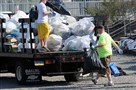 Workers clean up the Carnegie Science Center parking lot the morning after Kenny Chesney's 2013 concert at Heinz Field.