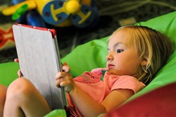 Lela Revercomb, 2, of Shade Gap, Pa., plays with an iPad during a media event in Lawrenceville in 2013.