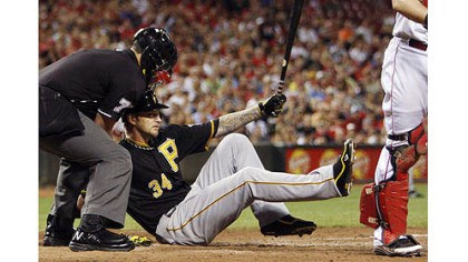 A.J. Burnett The Pirates' A.J. Burnett, center, falls to the ground after striking out with the bases loaded in the fourth inning. Home plate umpire Manny Gonzalez helps out at left.