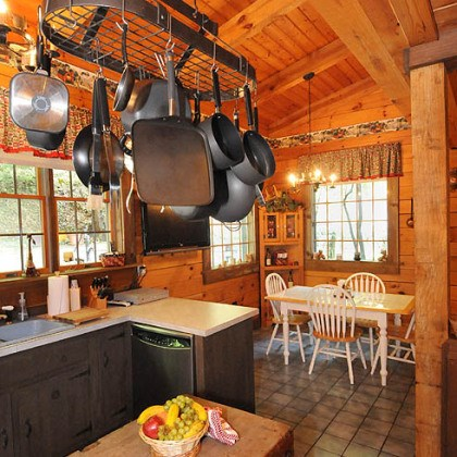 A rustic, natural-finish butcher block island A rustic, natural-finish butcher block island is topped by a hearty pot rack filled with pots in every size and shape -- both decorative and functional.