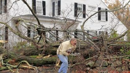 Andover, Mass. John Constantine makes his way out of his house after winds from Hurricane Sandy caused a tree to topple over and fall onto it Monday in Andover, Mass.