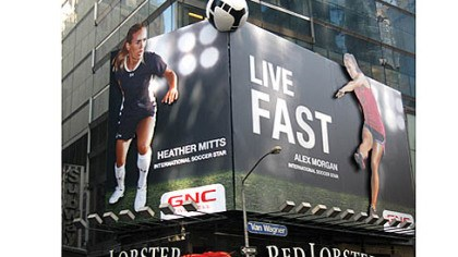 Billboard GNC's billboard in Times Square couldn't mention the Olympics and will have to black out the images of athletes Alex Morgan and Heather Mitts -- GNC brand ambassadors -- during the games.