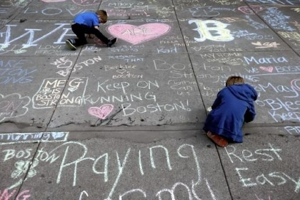 Chalk Two young boys leave messages with chalk Thursday on a sidewalk near the finish line of the Boston Marathon.
