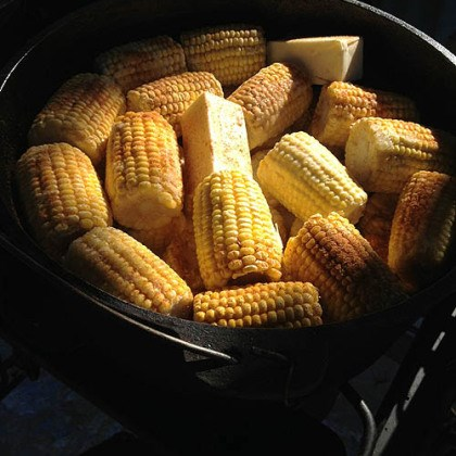 Corn A Dutch oven full of fresh corn on the cob, waiting to be cooked on top of hot coals.