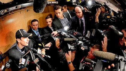 Crosby and reporters Sidney Crosby is besieged by the media at his locker after workouts this morning at the Consol.