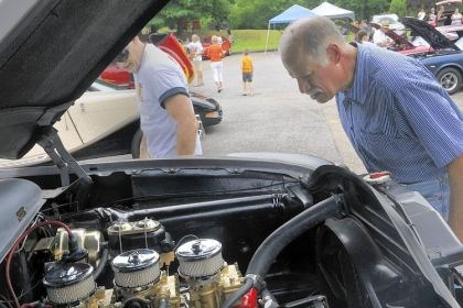 Cruise_10 Dave Cammarata of Pittsburgh looks at the small block Chevy engine with three carburetors tucked under the hood of a customized 1949 Ford at the St. Teresa of Avila Church car cruise in Ross.