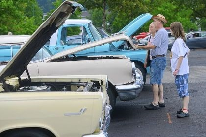"Cruise_5 Becky Hughes with her husband, Tony, and daughter, Sammy, of McKeesport check out a Pontiac during the Vintage Grand Pix car cruise. Mr. Hughes says the Grand Prix ""is the most fun you can have in Pittsburgh for free if you like cars."""