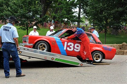 Datsun Driver Joe Maloy, of Bridgeville, pushes his 1968 Datsun 510 onto a tow truck after suffering a flat tire during the first race in Sunday's Pittsburgh Vintage Grand Prix race.