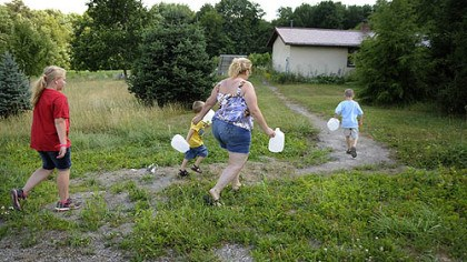 Fetching water Shelley Carlson, 42, center, walks to fill up gallon water jugs behind a Lutheran church camp several miles from her home in the Woodlands in June. A family friend, Kayla Zeidler, 10, left and two of Ms. Carlson's three sons, Dylan, 3, and Logan, 6, race to help her. Ms. Carlson noticed an odor and discoloration in her tap water in January 2011.