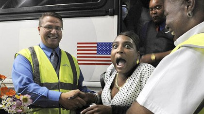 First passenger Alexis Brown, center, of Edenton, N.C., reacts as she is welcomed with flowers by Jeffery Driscoll, left, and Theresa Perry of Greyhound yesterday as the first passenger to arrive at Greyhound?s Pittsburgh station at the new Grant Street Transportation Center, Downtown. The $50 million center includes the bus terminal and two city parking garages, one of which also opened yesterday. Greyhound has been operating from a temporary terminal along Second Avenue during the center?s construction.