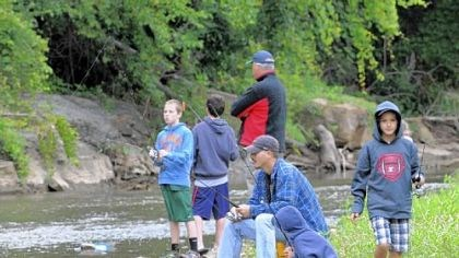 Fishing Contestants on Saturday in Heidelberg's first fishing tournament along Chartiers Creek included Bill Puccio of Scott, sitting, and his sons, David Puccio, 11, squatting next to his father, and Tyler Puccio, 9, at far right.
