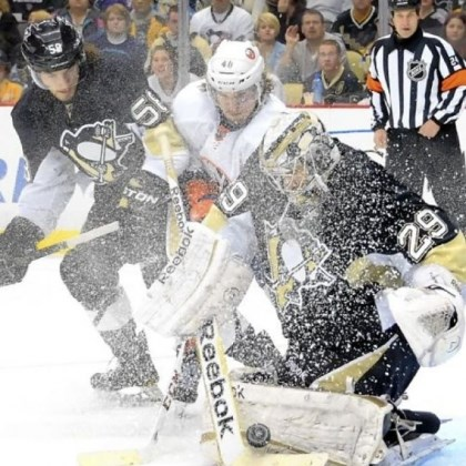 Fleury Goalie Marc-Andre Fleury somehow finds the puck through the ice storm kicked up by the Islanders' Michael Grabner in the second period Tuesday at Consol Energy Center.