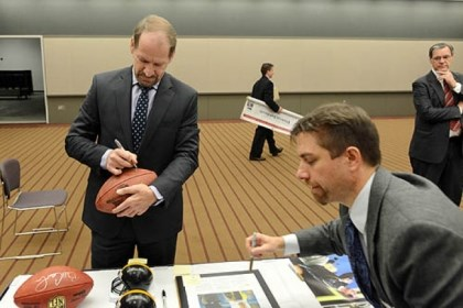 football Former Steelers Coach Bill Cowher signs a football to be auctioned off for charity.