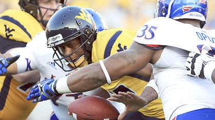 Geno Smith West Virginia quarterback Geno Smith is sacked by Kansas' Toben Opurum (35) and John Williams (71) during the second quarter.