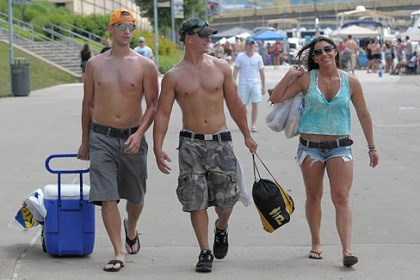 Getting ready Dan Jackson, left, Damian Truschel, and Heather Schultz, right, all of Penn Hills, walk along the North Shore as they prepare for the Kenny Chesney concert at Heinz Field.