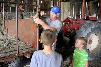 grandsons Dairy farmer Ralph Frye shows his grandsons, T.J. Frye, 7, left, and Matthew Frye, 5, how to hook a chain to the hay wagon during their visit to his Latrobe farm.