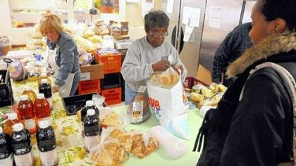 Helping hands Volunteers Mary Taylor, right, and D. Tolbert, left, help clients during the North Side food distribution.