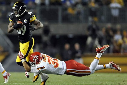 Jerricho Cotchery and Tysyn Hartman The Steelers' Jerricho Cotchery carries as he's defended by the Chiefs' Tysyn Hartman in the second quarter.