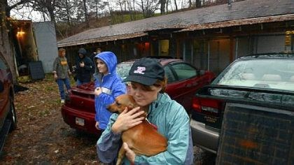 Kittanning Debbi Reefer carries Tinkerbell, a dachshund, as volunteers and the staff of Orphans of the Storm, an animal shelter in Kittanning that sits close to the Allegheny River, work to evacuate animals Monday in anticipation of possible flooding.