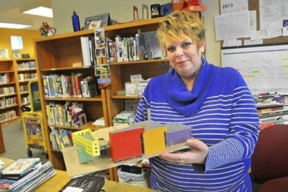 Library Jamie Cozza, a circulation assistant, displays a model of the planned renovation to the library building in Sharpsburg. It is expected to double in size following the receipt of a large state grant. The brown section is the existing structure.