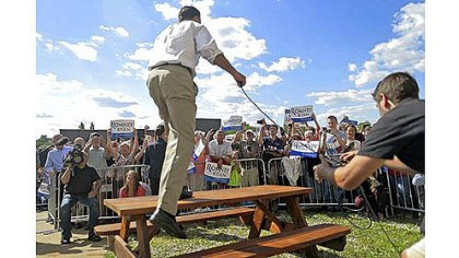 Mitt Romney An overflow crowd cheers as Republican presidential nominee Mitt Romney gets on a table to speak Monday as he campaigns at PR Machine Works in Ontario, Ohio.