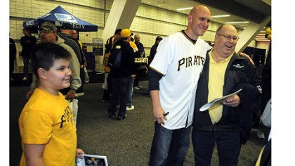 nicely Thomas Nicely, 12, of Delmont, left, watches his father Dennis Nicely get photographed by mom Christine (not in picture) with Pirates shortstop Clint Barmes at PirateFest at David L. Lawrence Convention Center.