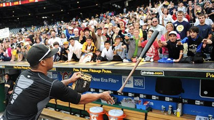 Pedro Alvarez Pedro Alvarez flips a bat to the top of the Pirates' dugout for a fan after the game Sunday. Several players tossed equipment and signed autographs.
