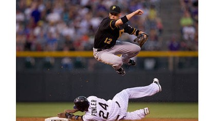 Pirates Pirates shortstop Clint Barmes jumps over a sliding Dexter Fowler after turning a double play in the third inning Tuesday night at Coors Field in Denver.