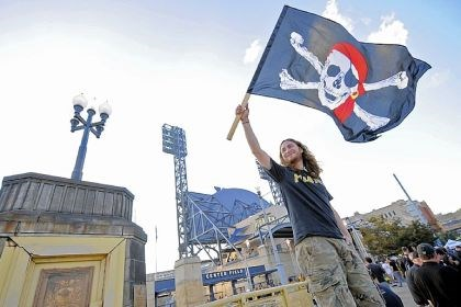 Pirates fan Derek Buck, 29, of Squirrel Hill waves the Jolly Roger on the Clemente Bridge before the game.