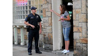 Pittsburgh police Pittsburgh police Officer Brett Butkewich of the Zone 3 station listens to comments from a concerned woman in the doorway of Mooney's Place on Brownsville Road in Carrick.