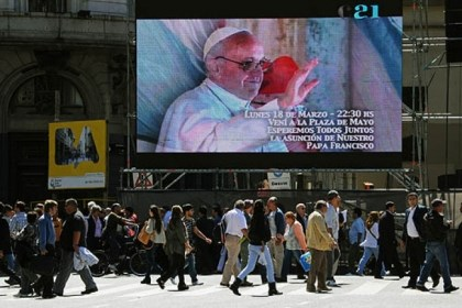 Pope Francis Argentine citizens walk in front of a giant screen placed next to the Buenos Aires Cathedral, where people will attend Pope Francis inauguration ceremony on live broadcast.