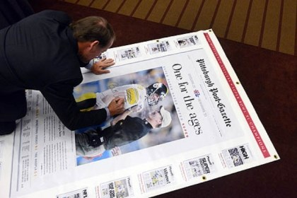 Post-Gazette edition Former Steelers Coach Bill Cowher signs a large replica of the Post-Gazette edition of his Super Bowl victory to be auctioned off for charity.