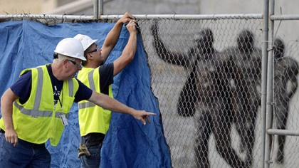 Preparing for removal Workers place a tarp on a fence in front of the statue of former Penn State football coach Joe Paterno before removing it.