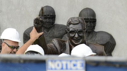 Removal Workers handle the statue of former Penn State football coach Joe Paterno before removing it.