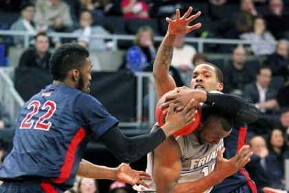 RMU1 Robert Morris forwards Lucky Jones, left, and Mike McFadden, right, pressure Providence forward Kadeem Batts into a traveling violation in the first half in Providence, R.I.