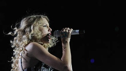 Singing Taylor Swift belts out a song.