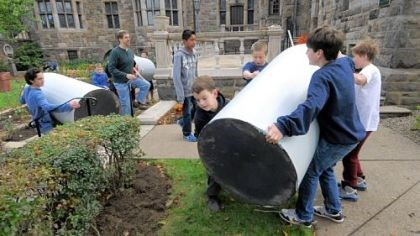 Squirrel Hill Sixth-graders move rain barrels at Temple Sinai's rainwater garden in Squirrel Hill.