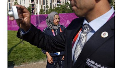 Tahmina Kohistani A man takes a photo near Tahmina Kohistani, Afghanistan's only female athlete, after attending the Olympic Team Welcome Ceremony at the Athletes' Village.