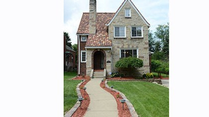 The brick-and-stone Tudor-style house The brick-and-stone Tudor-style house, built in 1925, has many of the same architectural details as nearby houses, including a tile roof, hardwood floors, pointed Tudor arches between rooms and large covered side porch.
